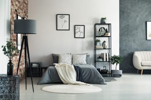 Vase on metal table and grey lamp in spacious bedroom with white carpet and gallery on wall above bed
